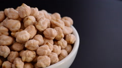 Chickpeas vegetables gyrating on black background justified at left Stock Footage