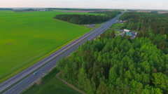 Aerial View. Flying over the green sown field along the road with cars. Stock Footage