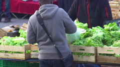 Young male buying fresh greens at the local market, organic food, eco products Stock Footage