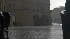 Raindrops falling on asphalt in old European city, people walking, rainy weather Stock Footage