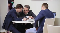 Three businessmen sitting at the table and discuss the case Stock Footage