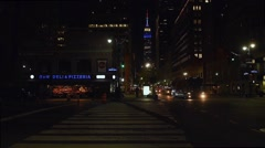 Empire State Building: Nighttime, red, white, blue w/ New Yorker Hotel in foregr - stock footage