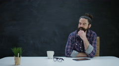 4K Pensive hipster man with computer tablet on blank chalkboard background Stock Footage