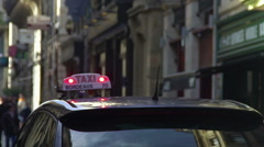 Taxi car driving down the street in old European city, transportation services Stock Footage