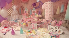 Sweets and decorations on the table to celebrate 1 year baby Stock Footage