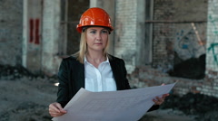 Architect builder engineer builder of ruined building looking girl work plan for Stock Footage