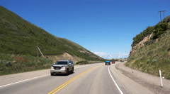 POV-Driving 2-lane mountains approaching giant wind turbines Stock Footage