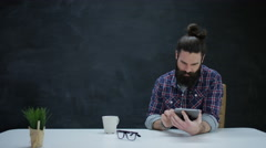 4K Pensive hipster man using computer tablet on blank chalkboard background Stock Footage