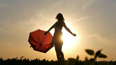 Portrait of a beautiful girl with a red umbrella in the sunset smiling emotions Stock Footage