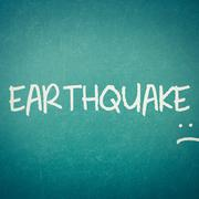 Green blackboard wall texture with a word Earthquake - stock photo