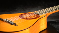 Ancient pear guitar manufactured by a luthier gyrating on black velvet - stock footage