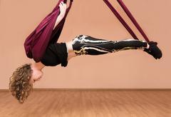 Woman making aerial yoga exercises Stock Photos