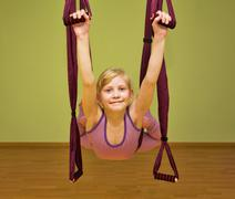 Little girl making aerial yoga exercises, indoor Stock Photos