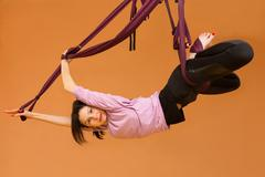 Woman making aerial yoga exercises, indoor - stock photo