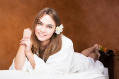 Smiling attractive young woman in a white robe Stock Photos