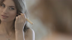 Beautiful girl standing before the mirror and applying the powder on the face - stock footage