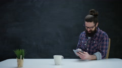 4K Portrait smiling hipster man using computer tablet on chalkboard background Stock Footage