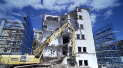 Clouds move hurried over huge excavator and destroyed building - stock footage