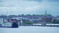 Cargo ship maneuvers around a port city in Germany Stock Footage