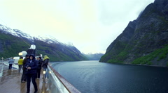 Cruises with tourists on the deck passes Norwegian fjord Stock Footage
