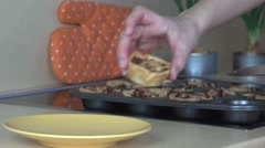 Baker hands take out baked meat cup cakess from cookie sheet and put in dish Stock Footage