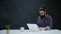 4K Hipster man using laptop computer & thinking on blank chalkboard background Arkistovideo