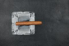 Glass ashtray and cigar on a black natural leather - stock photo