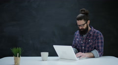 4K Portrait smiling hipster man using laptop on blank chalkboard background Stock Footage