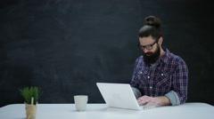 4K Portrait smiling hipster man using laptop on blank chalkboard background Stock Footage