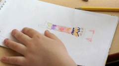 Little girl draws a pictures in the copybook Stock Footage