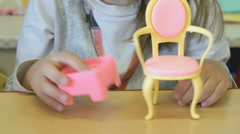 Little girl playing children's furniture at table - stock footage