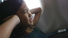 Nervous Asian girl sitting at the airplane and covering ears with hands Stock Footage