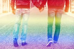 two men holding hands with the rainbow colors for gay pride - stock photo
