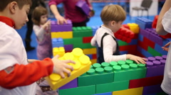 Children build a house out of Lego Stock Footage