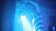 Man dancing in the night club. Spotlight. By turns illuminates the lights Stock Footage