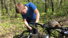 Boy repairing a bicycle in the woods Stock Footage