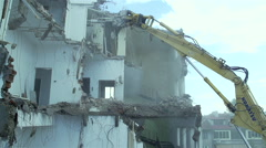 A huge mechanical arm of the excavator destroys apartment building in slow Stock Footage