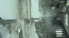 Pieces of concrete and water jet falling in slow motion from ruined building. Stock Footage