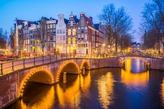 Amsterdam canals with bridge and typical dutch houses in Netherlands Stock Photos