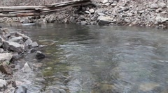 Spring stream with floating pieces of ice and with small bridge - stock footage