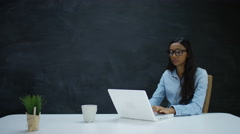 4K Thoughtful woman working on laptop on blank chalkboard background Stock Footage