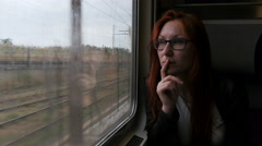 4K Attractive woman in thought looking out of a train window - stock footage