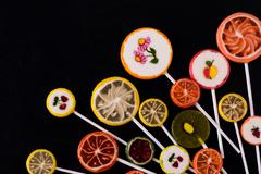 Colorful candies and lollipops over stone background. Top view with copy spac - stock photo