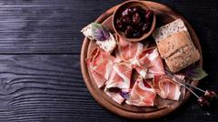 Curled Slices of Delicious Prosciutto with spice  Italian cuisine - stock photo