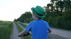 Boy in hat rides a bicycle on the nature of the evening  slow motion back view Stock Footage