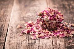 Rose petals and dried flowers in spoon on old wooden table Stock Photos