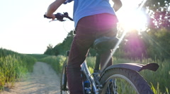 boy in hat rides a bicycle on the nature of the evening  slow motion back view - stock footage