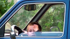 Kid jumping on the front seat of a car Stock Footage