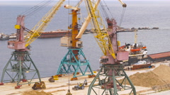 Industrial port area. Crane with bucket loads mortar sand in the truck Stock Footage