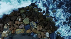 Vertical video, a surfer on the rocks with waves. Aerial drone video N. Stock Footage